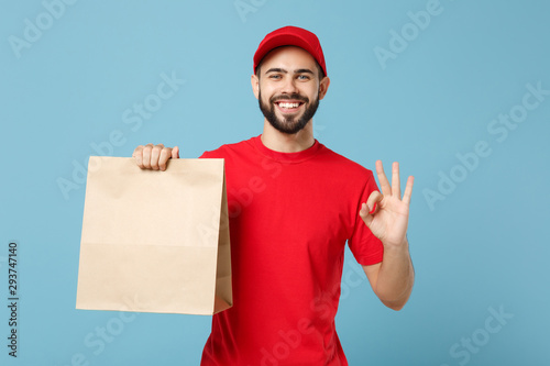 Fototapeta Delivery man in red uniform hold craft paper packet with food isolated on blue background, studio portrait. Male employee in cap t-shirt print working as courier. Service concept. Mock up copy space. obraz