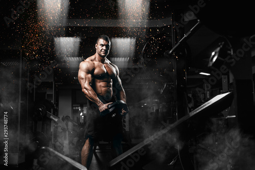 Muscular man bodybuilder training in gym and posing Wallpaper Mural