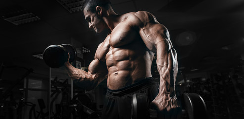 Fototapeta na wymiar Muscular athletic bodybuilder fitness model training arms with dumbbells in gym. Concept sport photo of exercises in gym