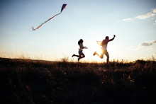 Young Couple Have Fun With Kite. They Send Genuine Emotions  To The World.