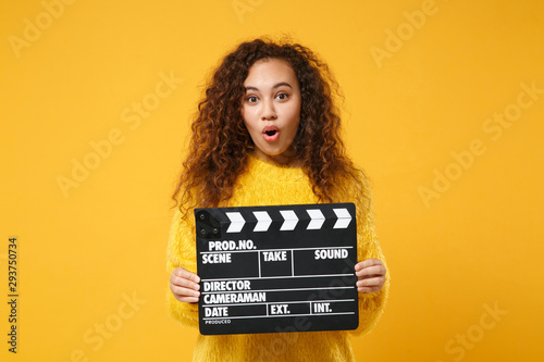 Fotografie, Obraz  Shocked young african american girl in fur sweater posing isolated on yellow orange background in studio