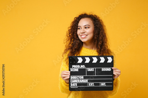 Fotografie, Obraz  Smiling young african american girl in fur sweater posing isolated on yellow orange background in studio