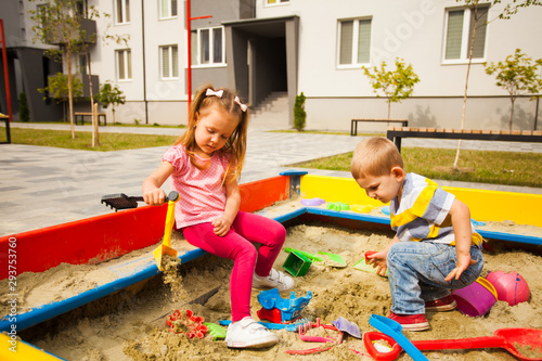 Adorable little girl playing in a sandbox Wallpaper Mural