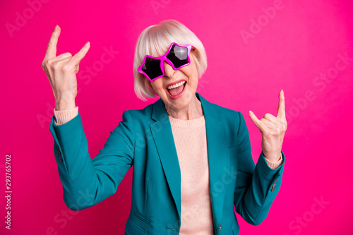 Photo of screaming white haired shouting rocking mature woman wearing beige sweater green jacket star shaped pink spectacles isolated over maroon vivid color background - 293765702
