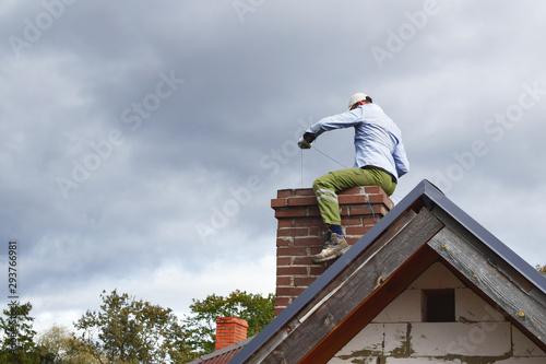 Valokuvatapetti Chimney sweep man cleaning brown brick chimney while sitting on chimney on building roof on cloudy sky background with copy space for text