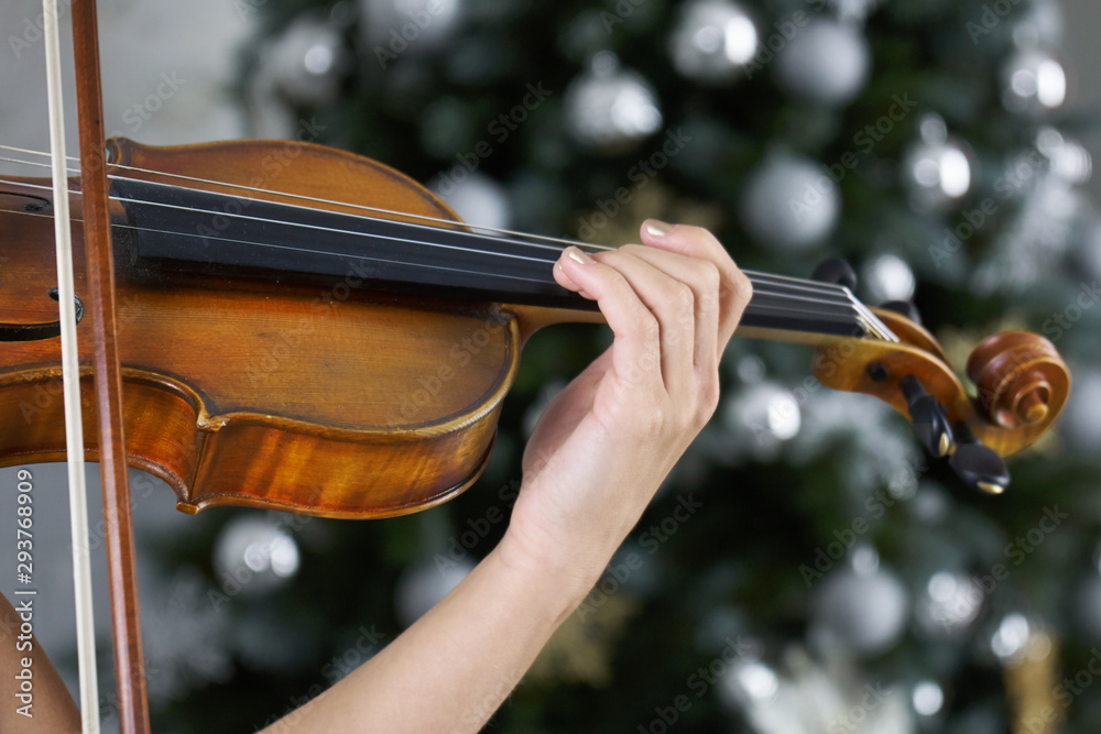Hand of a female violinist on the fingerboard of a violin takes a chord with a decorated Christmas tree on the background.Classical music concert on Christmas or New Year eve