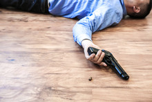 Office Worker Lies On The Floor Holding Gun In His Hands. Suicide Because Of Work Stress. Depression Or Burnout. Terrible Life Situation. Man Near The Laptop At The Desk.