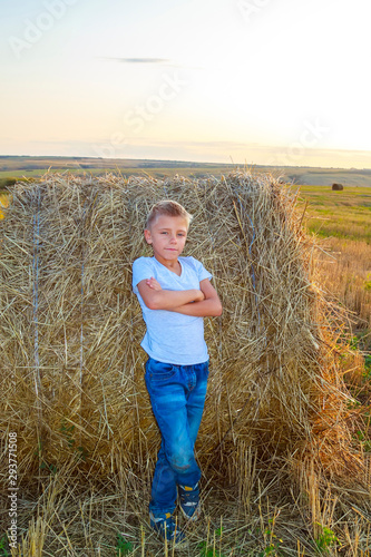 Fototapeta smiling boy standing at haystack at sunset