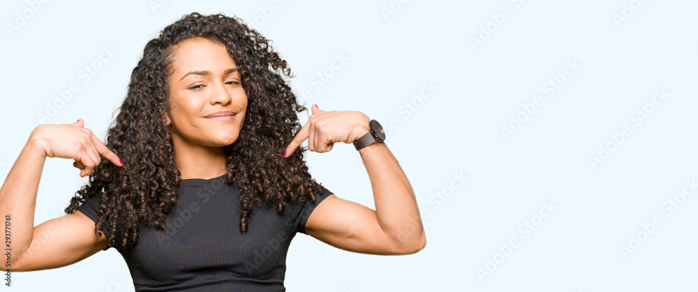 Fototapeta Young beautiful woman with curly hair looking confident with smile on face, pointing oneself with fingers proud and happy.