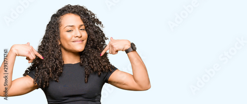 Fotografie, Obraz Young beautiful woman with curly hair looking confident with smile on face, pointing oneself with fingers proud and happy