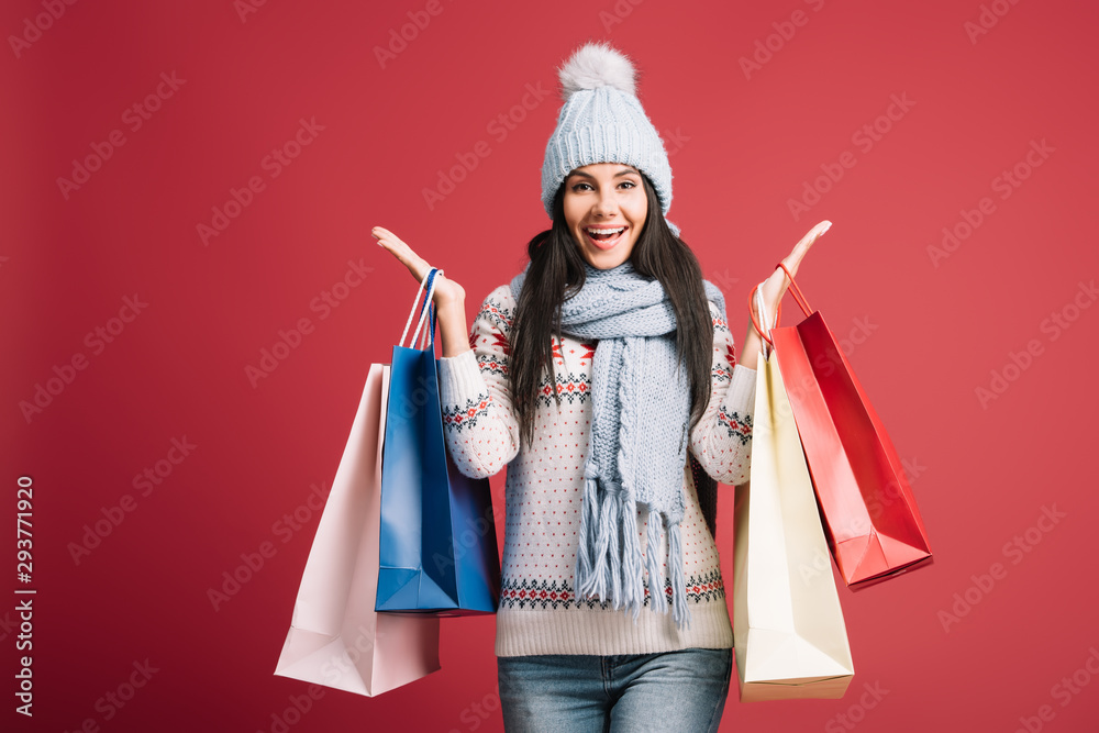 Fototapeta excited woman in winter sweater, scarf and hat holding shopping bags, isolated on red