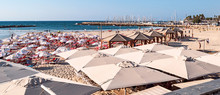 Tourists Enjoying The Beach And Sun Shade Umbrellas At Gordon Beach In Tel Aviv With The Marina And Sailboats In The Background