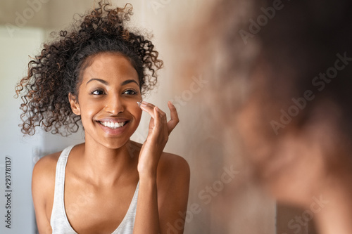 Young black woman applying skin cream Fotobehang