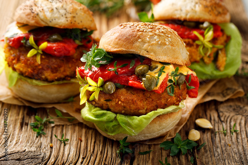 Pumpkin burgers with the addition of grilled peppers, fresh lettuce, herbs and capers on a wooden rustic background, close-up. Vegan burgers