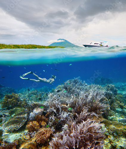 Staande foto Koraalriffen Divers views beautiful coral reef with many fish near Bunaken island, Indonesia.