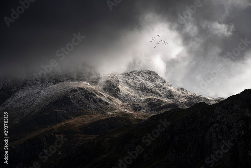 Fototapeta Stunning moody dramatic Winter landscape image of snowcapped Tryfan mountain in
