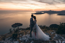 The Bride And Groom Admire The Beautiful Natural Landscape In Montenegro Near The Island Of Sveti Stefan.
