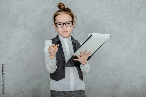 Little girl with a folder in her hands on a gray background Fototapeta