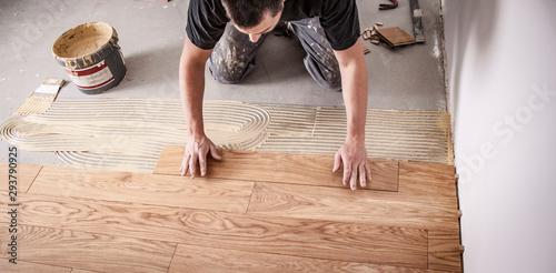 Obraz Handwerker verlegt Parkettboden - fototapety do salonu
