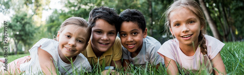Fototapeta panoramic shot of cute multicultural children lying on grass obraz