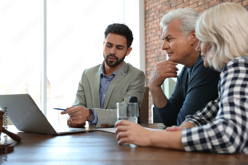 Fototapeta Male notary working with mature couple in office