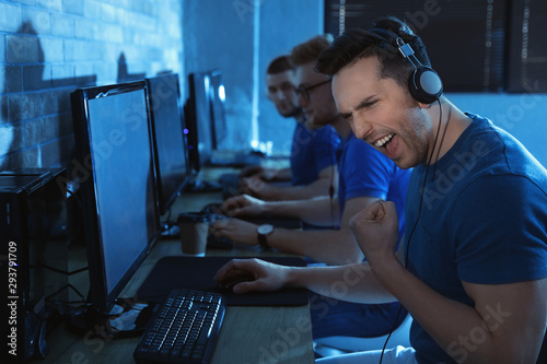 Photo Group of people playing video games in internet cafe