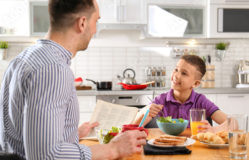 Dad and son having breakfast together in kitchen