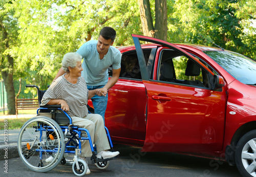 Fotomural  Young man helping disabled senior woman in wheelchair to get into car outdoors