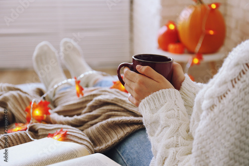 Top view of woman relaxing on couch at home, drinking latte. Cozy evening at home. Young woman enjoying alone time, sitting on sofa covered with soft blanket. Close up, copy space. - 293805748