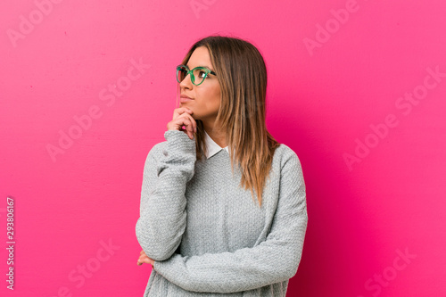 Fotografiet  Young authentic charismatic real people woman against a wall looking sideways with doubtful and skeptical expression