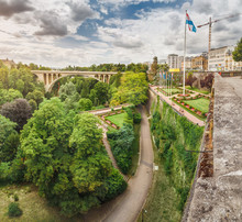 Panoramic City View Of Luxembourg City With The Famous Adolphe Bridge And Constitution Square And Park