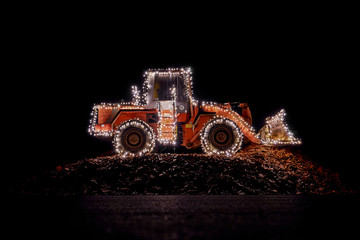 Blurred wheel loader decorated with lights at christmas