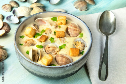 Fényképezés Clam chowder with fresh parsley and croutons, with shells on a blue background