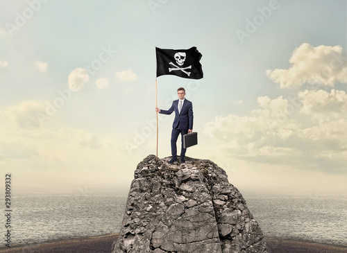 Photo Successful businessman on the top of a mountain holding pirate flag