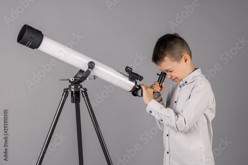 Foto young astronomer looks through a telescope and writes in the tablet