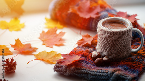 Papiers peints Cafe Mug of hot coffee with knitted warm sweater and autumn leaves on the window in the house. Hygge concept