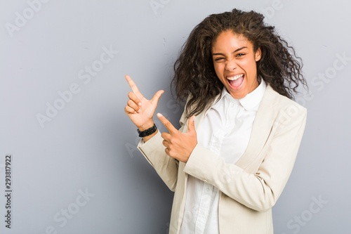 Young african american business woman pointing with forefingers to a copy space, expressing excitement and desire.