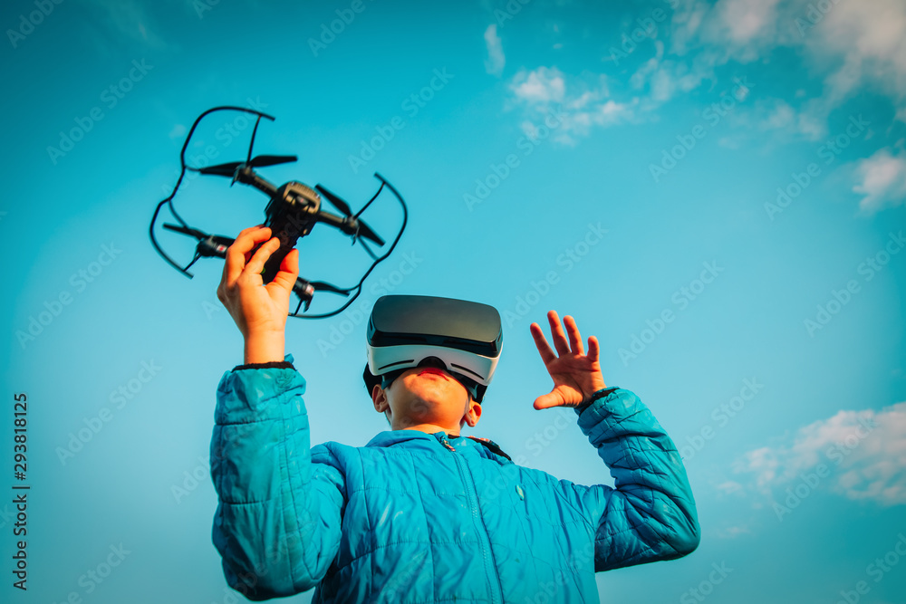 Fototapeta Young boy flying drone in virtual reality glasses in nature