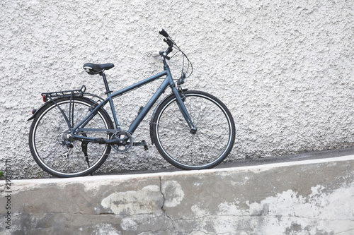One gray bicycle standing against white plastered wall © Nadya So