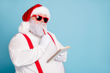 Close up photo of focused funny funky fat santa claus hold notebook think about wish list plan decide what choose look thoughtful wear stylish trendy suspenders isolated over blue color background