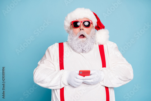 Close up photo of amazed funny funky overweight white hair long bearded santa claus hipster use cell phone search winter discount text sms wear red suspenders isolated over blue color background
