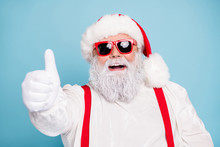 Close Up Photo Of Funny Funky Fat Overweight Santa Claus Have Modern Hipster Eyeglasses Show Thumb Up Recommend Winter Season Sales Wear Red Suspenders Overalls Isolated Over Blue Color Background