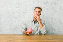 Young Man Saving Money With A Piggy Bank Yawning Showing A Tired Gesture Covering Mouth With Hand.
