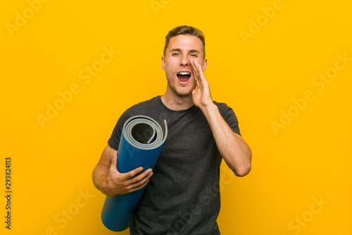 Photo  Young caucasian man holding a mat shouting excited to front.