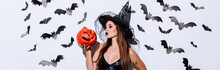 Panoramic Shot Of Girl In Black Witch Halloween Costume Kissing Carved Spooky Pumpkin Near White Wall With Decorative Bats