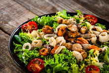 Salad With Seafood And Vegetables On Wooden Table