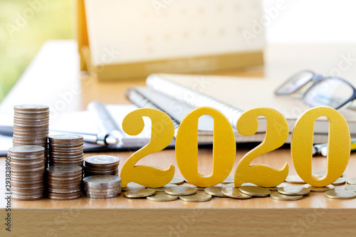 Fototapeta Word 2020 put on coins with coins stack on desk .Savings New year Concept. obraz