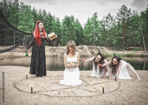 Beautiful witch making witchcraft with horned demons and victim Billede på lærred