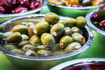 marinated and stuffed olives are on display in a store or in the kitchen of a restaurant