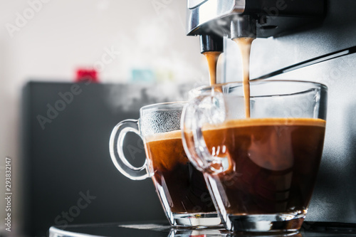 Fotografija freshly brewed coffee is poured from the coffee machine into glass cups in the k